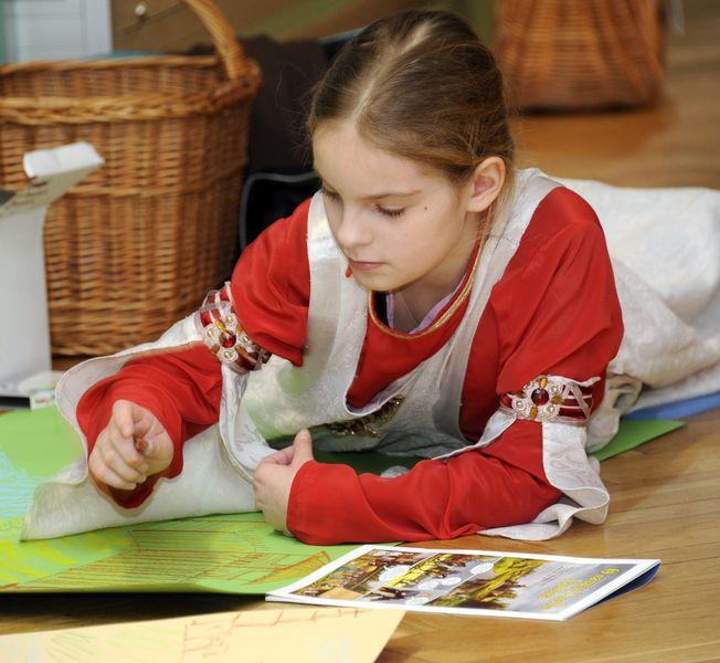 Zajęcia edukacyjne, Dziewczynka rysuje kredkami na kolorowym papierze.