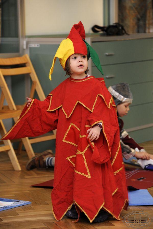 Zdjęcie z zajęć edukacyjnych. Kilkuletni chłopiec w czerownym przebraniu i kolorowej czapce.