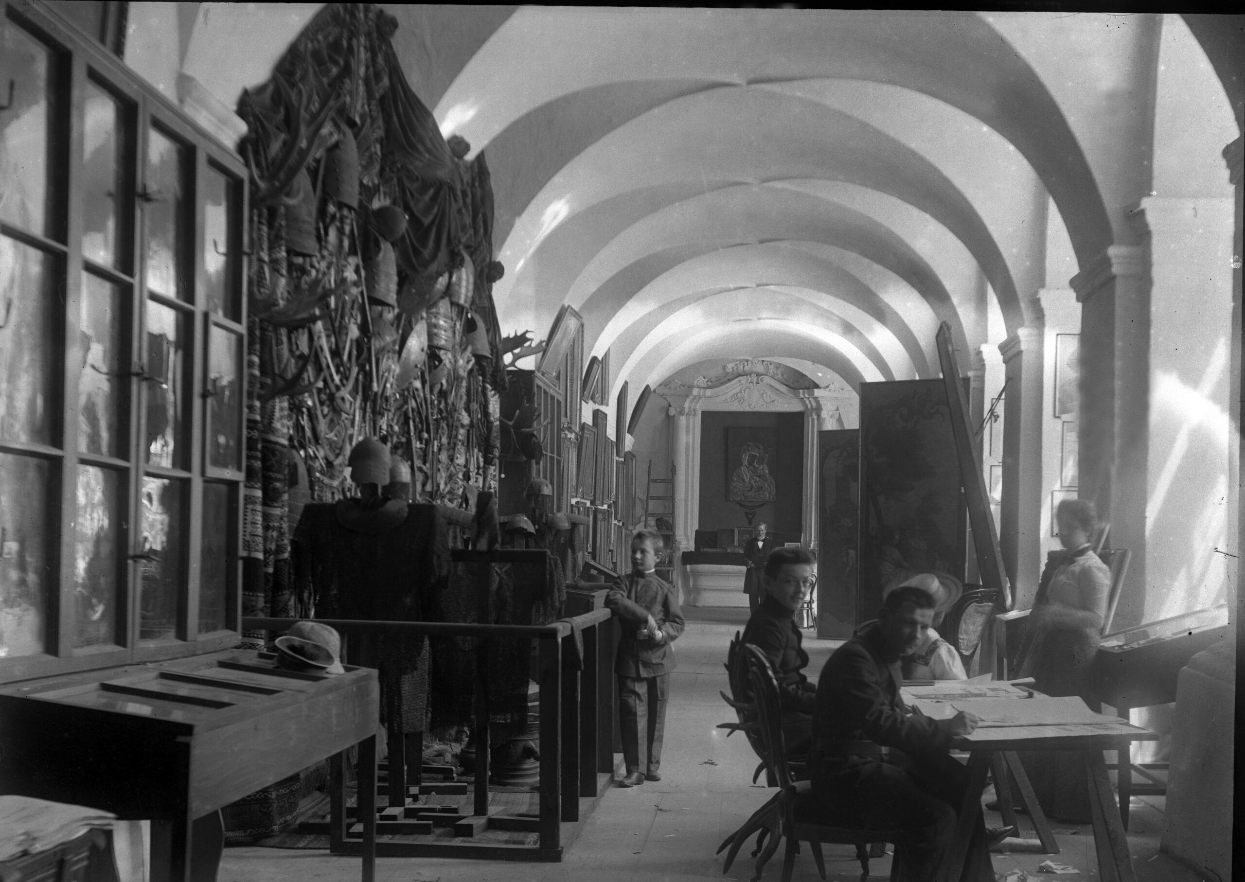 Czarnobiała fotografia ekspozycji muzealnej. Po prawej przy stołach siedzące osoby, po lewej gabloty i eksponaty zawieszone na ścianach.