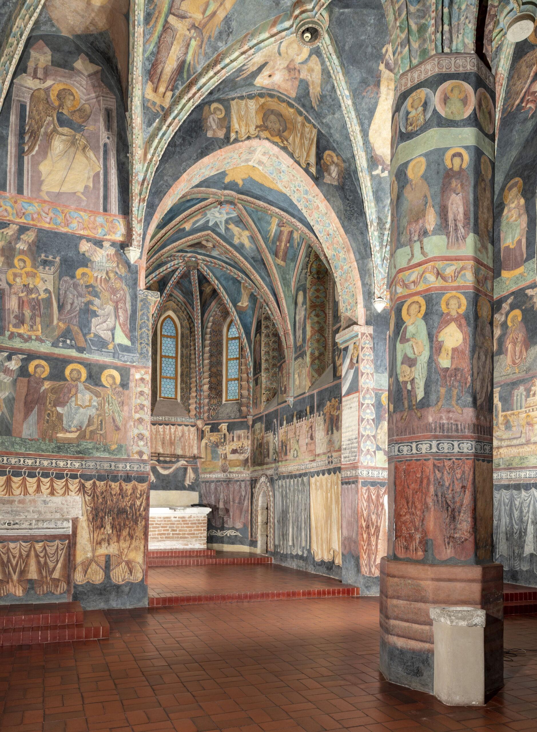 Fotografia wnętrza kaplicy. Ceglana podłoga. Po prawej filar podtrzymujący sklepienie. Ściany i sufit ozdobione kolorowymi malowidłami o tematyce religijnej.