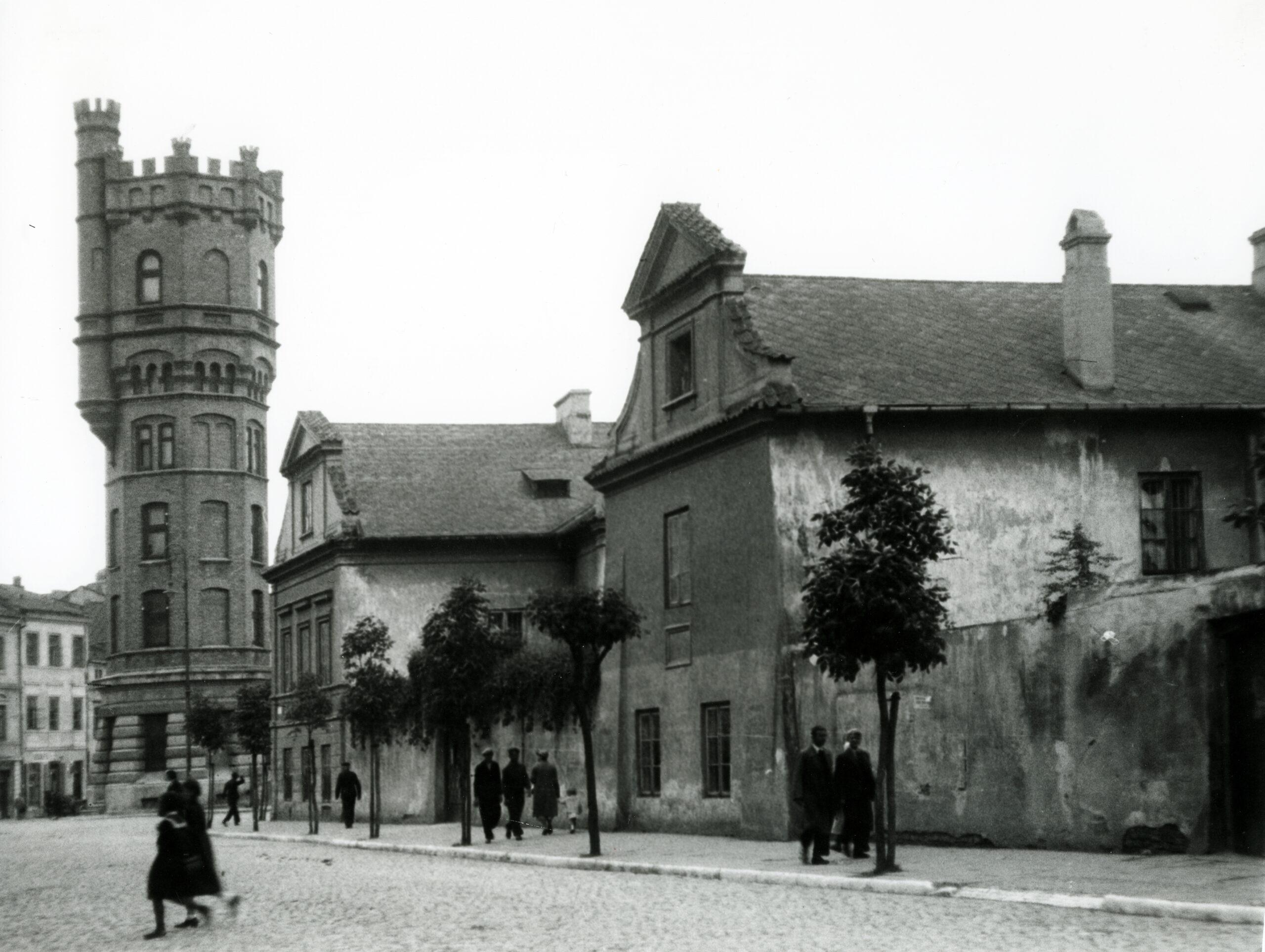 Fotografia czarnobiała z widokiem na ulicę oraz przylegające do niej budynki - z lewej wieża ciśnień, po prawej