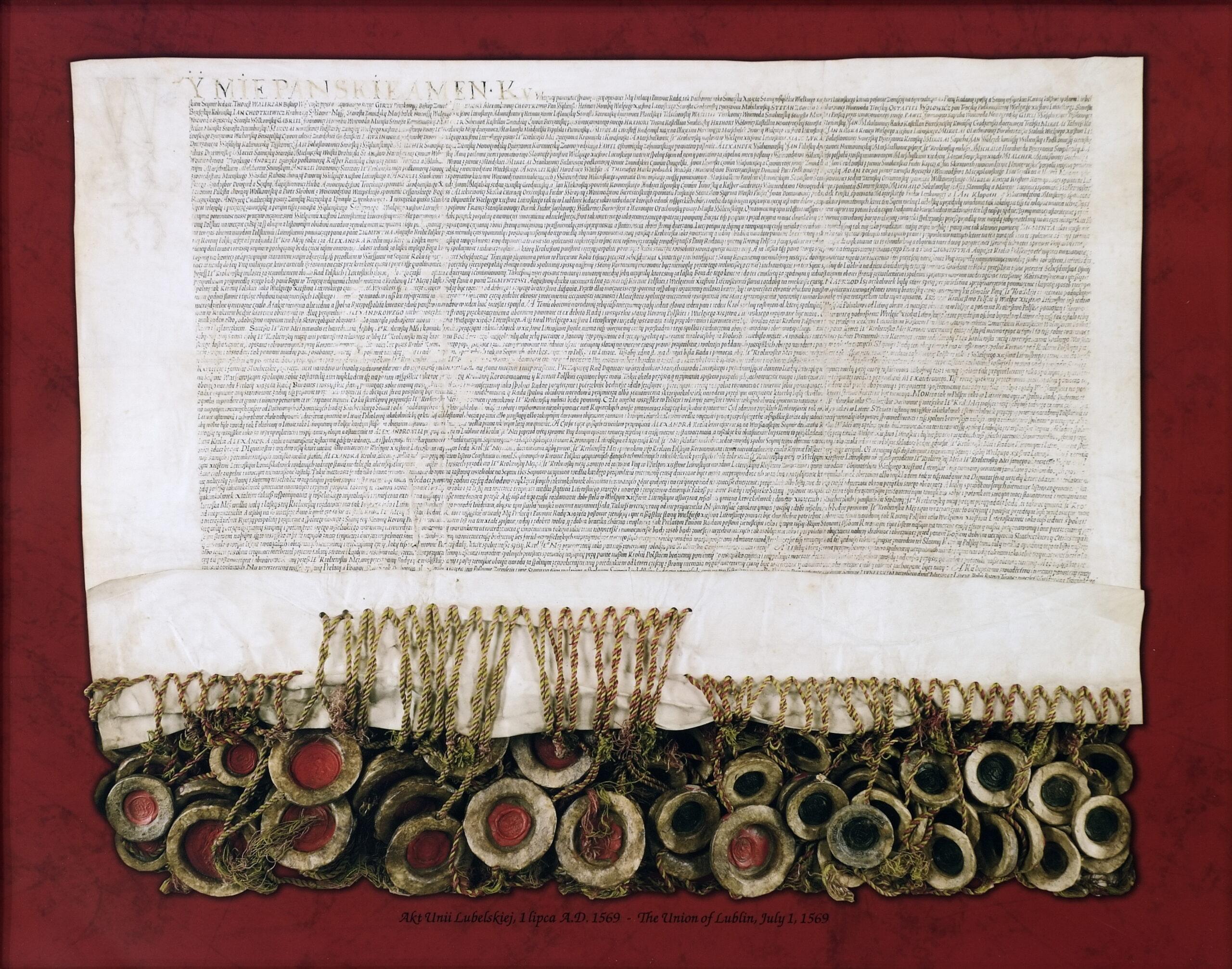 Reprodukcja aktu unii lubelskiej. Na kremowym papierze pisany ręcznie tekst. U dołu dokumentu zawieszone lakowe pieczęci na sznurkach.
