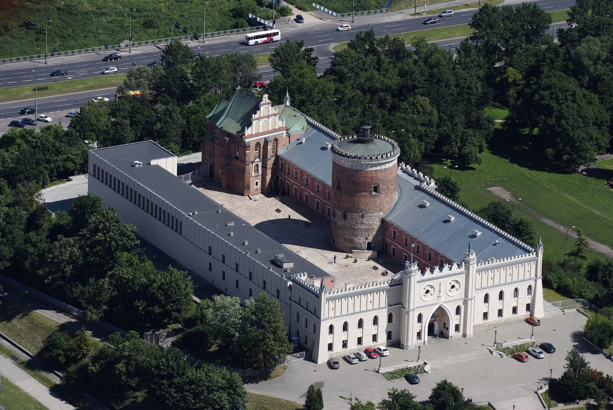 Fotografia. Widok z lotu ptaka na wzgórze zamkowe - budynek muzeum w kształcie litery U oraz przylegające do niego budowle - wieżę oraz kaplicę.