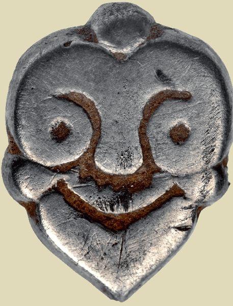 Zdjęcie archeologicznego obiektu wyglądającego jak metalowa twarz