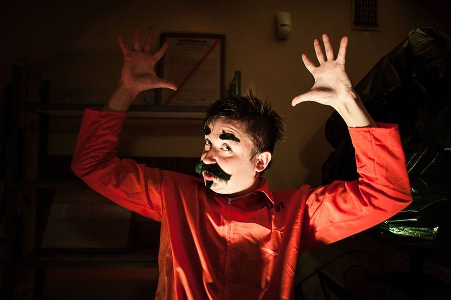 Zdjęcie mężczyzny z doklejonymi ciemnymi brwiami, wąsami i brodą, ubranego w czerwoną koszulę, z wyciągniętymi do góry rękami o rozstawionych palcach