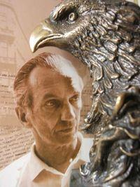 Zdjęcie twarzy starszego mężczyzny, obok niego rzeźbiona głowa orła