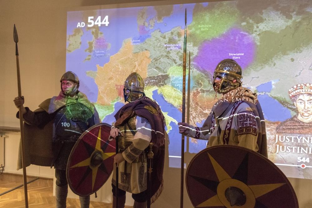 Zdjęcie przedstawia trzech mężczyzn w historycznych strojach: na głowach mają hełmy, w rękach trzymają tarcze i włócznie, na kolczugach zarzucone płaszcze. W tle projekcja mapy świata.