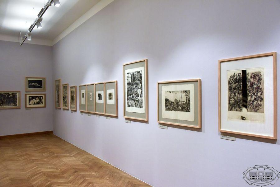 Widok na salę wystawową. Na ścianie wiszą czarno-białe grafiki oprawione w drewniane ramy.
