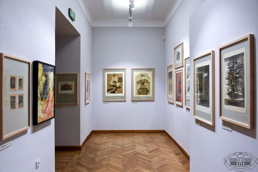 Sala wystawowa. Na białych ścianach grafiki oprawione w drewniane ramy.