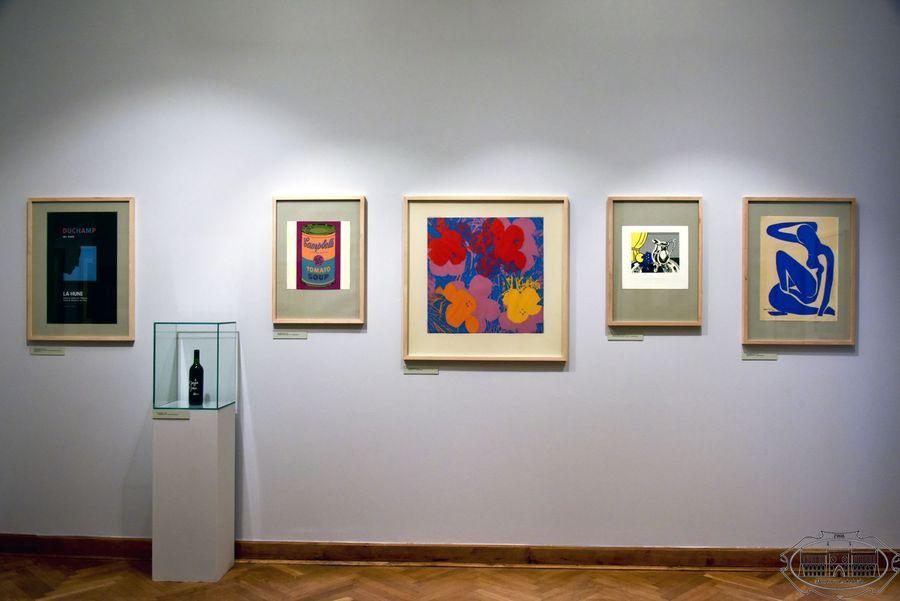 Na białej ścianie wisi pięć kolorowych grafik oprawionych w drewniane ramy. Z lewej strony w szklanej gablocie stoi butelka.