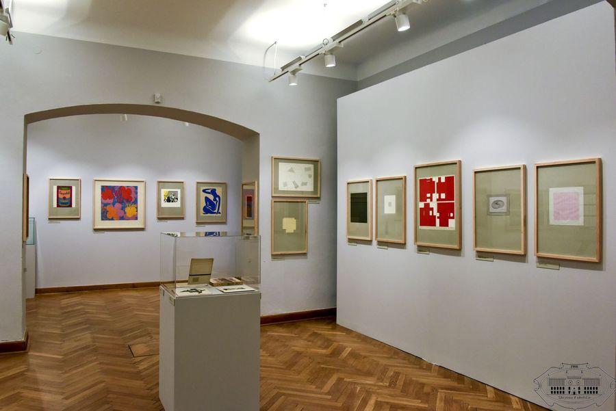 Widok na salę wystawową. Białe ściany, drewniana podłoga. W centrum kubik ze szlaną gablotą z eksponatami. Na ścianach wiszą kolorowe grafiki.