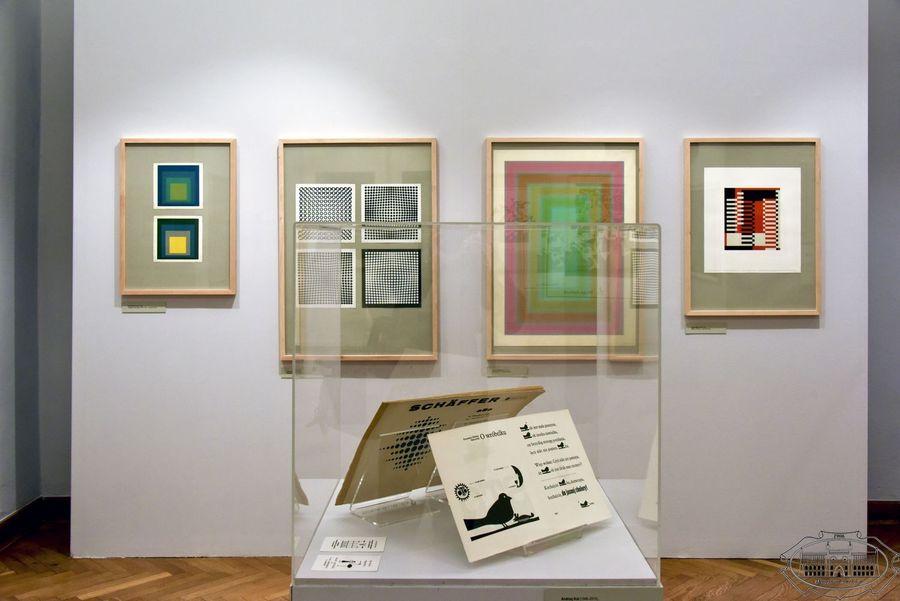 W centrum szklana gablota z grafikami. W tle wiszą cztery grafiki oprawione w drewniane ramy. Prace charakteryzują geometryczne motywy.