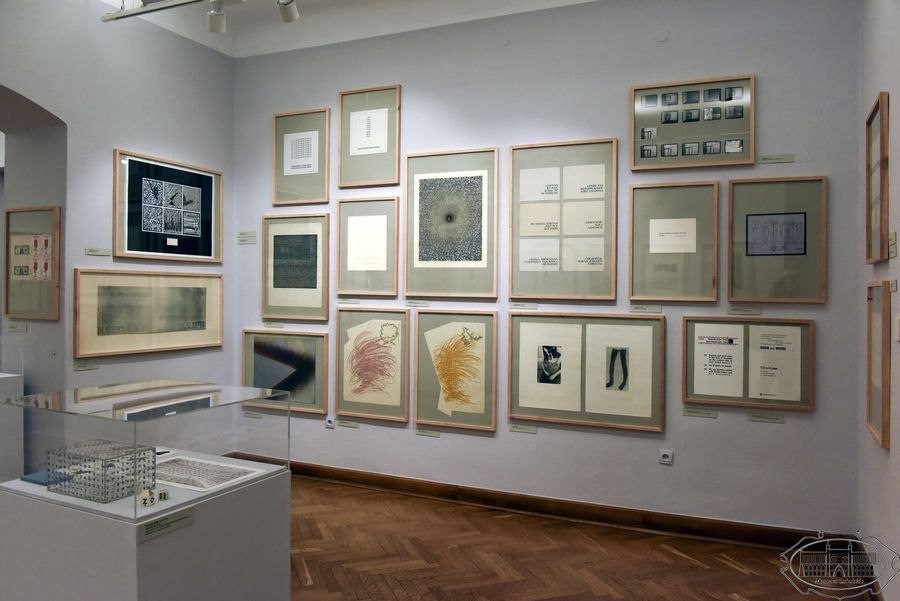 Sala wystawowa. Na ścianach wisi kilkanaście grafik oprawionych w drewniane ramy. W lewym dolnym rogu szklana gablota, w środku m.in. geometryczny obiekt.