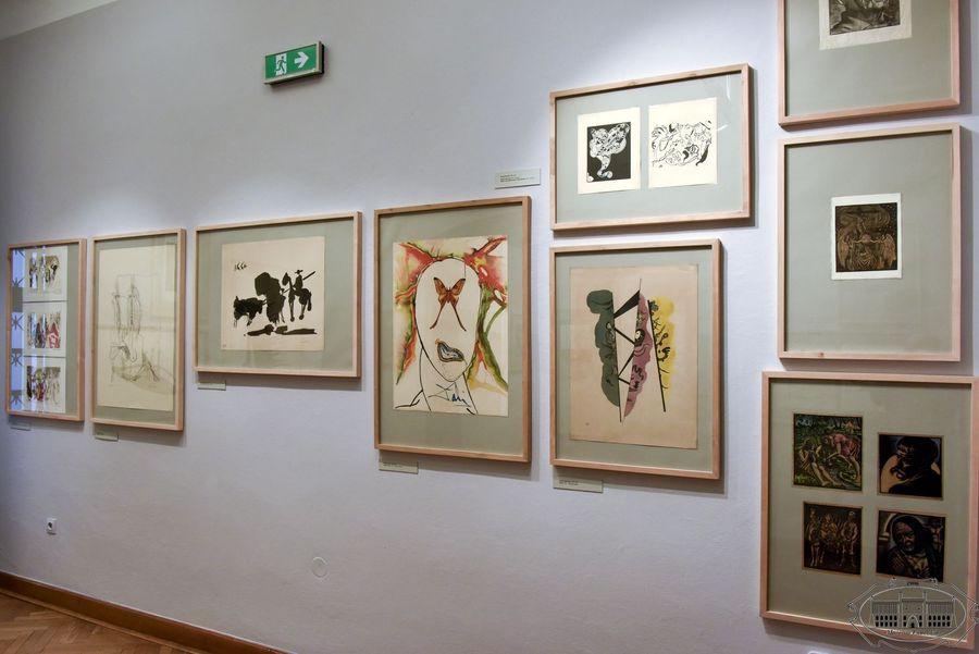 Na ścianie wiszą kolorowe, oprawione grafiki.