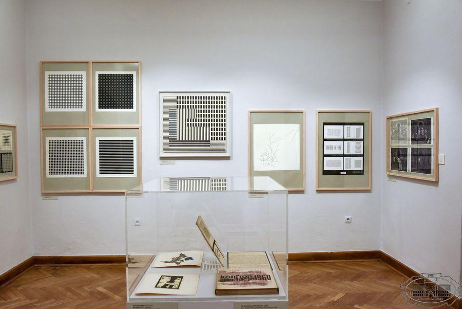 W centrum gablota z książkami. W tle na ścianie wisi dziesięć czarno-białych grafik.