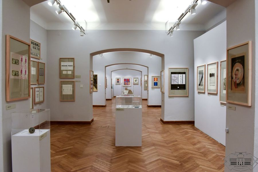 Widok ogólny na salę wystawową. Na ścianach wiszą grafiki. W centrum stoją białe kubiki zwieńczone szklanymi gablotami.