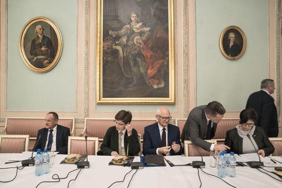 Członkowie Rady siedzą przy stole, przed nimi notatki i mikrofony. W tle na ścianie wiszą obrazy.