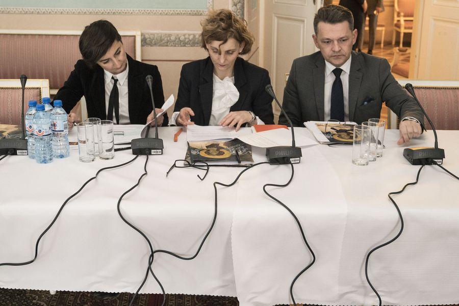 Trzech członków Rady, dwie kobiety i jeden mężczyzna, siedzą przy stole i patrzą w notatki. Przed nimi mikrofony.