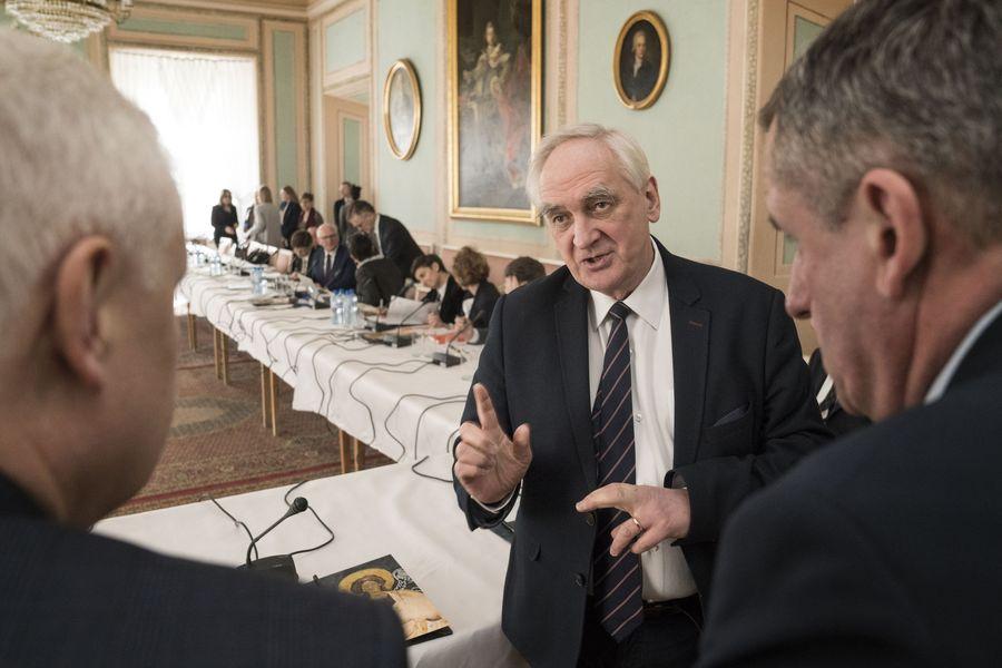 Mężczyzna ubrany w garnitur rozmawia z dwoma mężczyznami widocznymi od tyłu. W tle członkowie Rady przy stole.