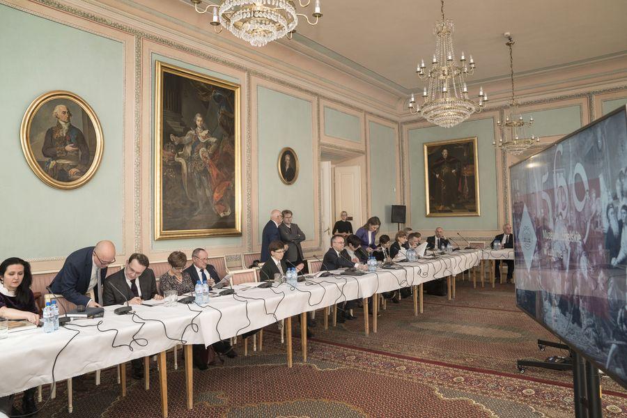Członkowie Rady siedzą przy stole. Niektórzy stoją. W tle wiszące na ścianie obrazy.