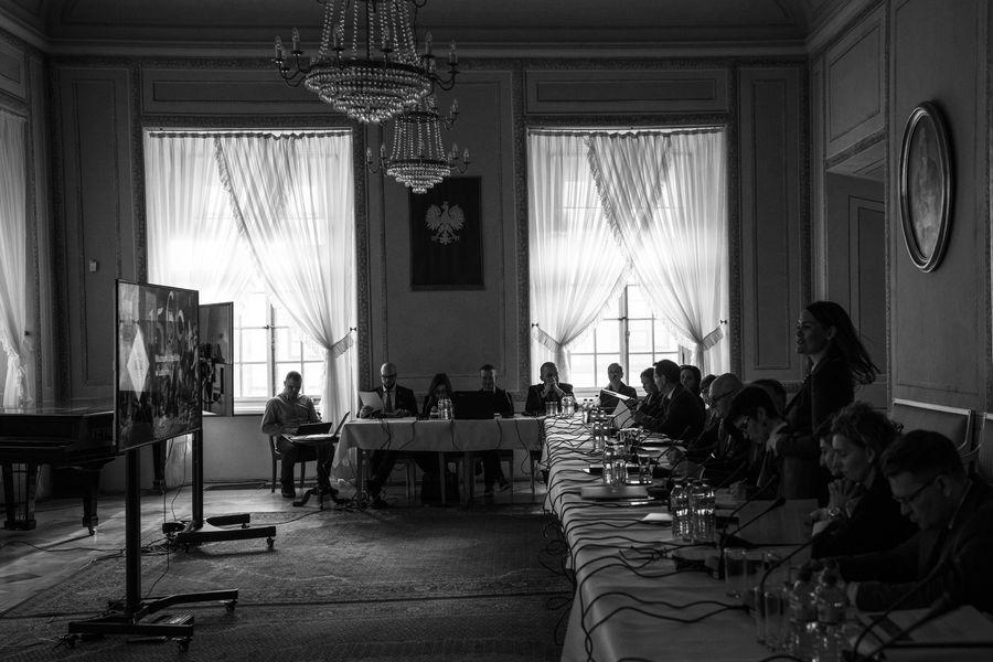 Czarno-białe zdjęcie ukazujące członków Rady siedzących przy stole. Dyrektor Katarzyna Mieczkowska stoi i przemawia.