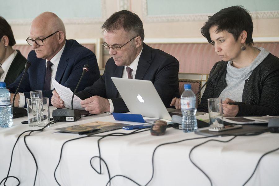 Trzech członków Rady, jedna kobieta i dwóch mężczyzn, siedzą przy stole i czytają.