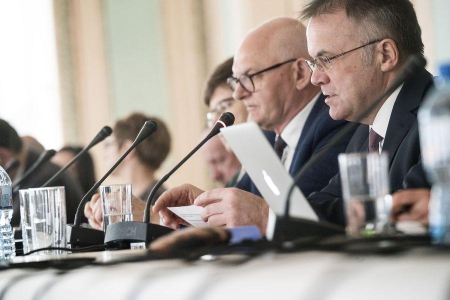 Zbliżenie na twarze dwóch mężczyzn siedzących przy stole, przed nimi mikrofony.