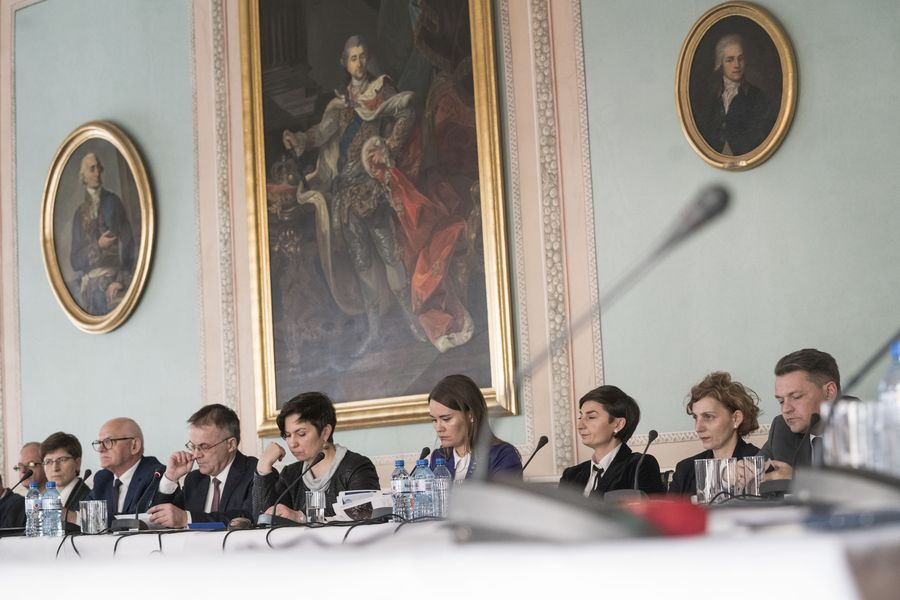 Członkowie Rady siedzą przy stole, w tle obrazy.