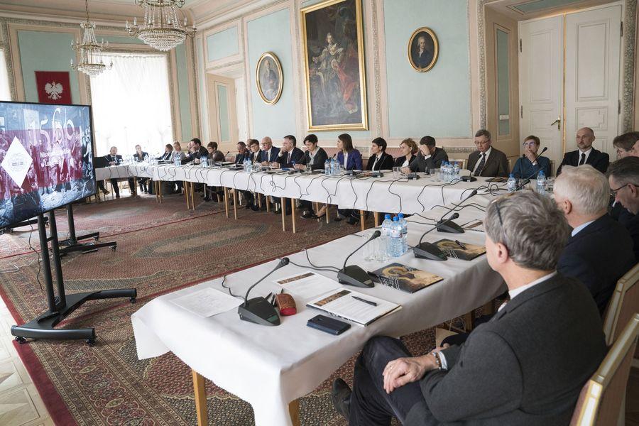 Widok na salę z długim, przykrytym białym obrusem stołem. Przy stole siedzą członkowie Rady.