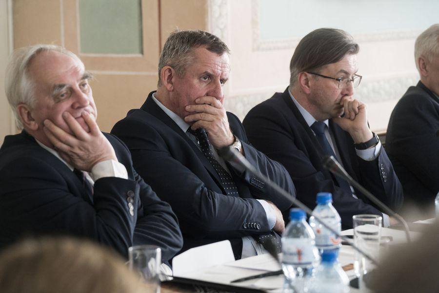 Zbliżenie na członków Rady - trzech mężczyzn siedzi przy stole, dotykają swojej twarzy, podpierając głowę.