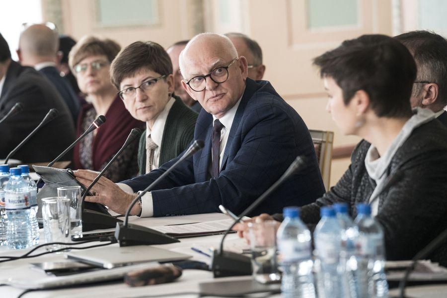 Zbliżenie na twarze rozmawiających członków Rady.  W centrum mężczyzna, po bokach kobiety. Siedzą przy stole, przed nimi mikrofony.