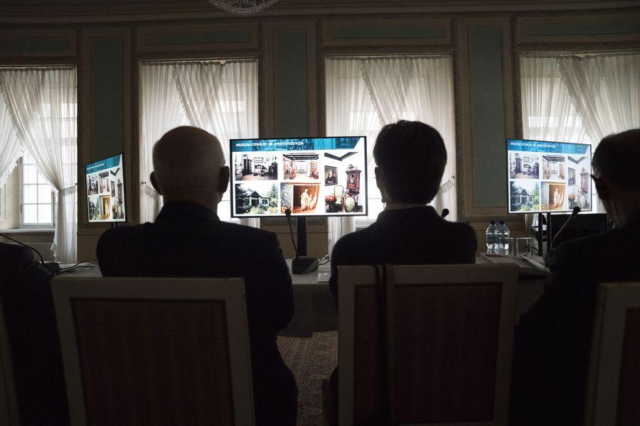 Trzy postaci widoczne od tyłu, siedzą na krzesłach, przed nimi ekrany monitorów.