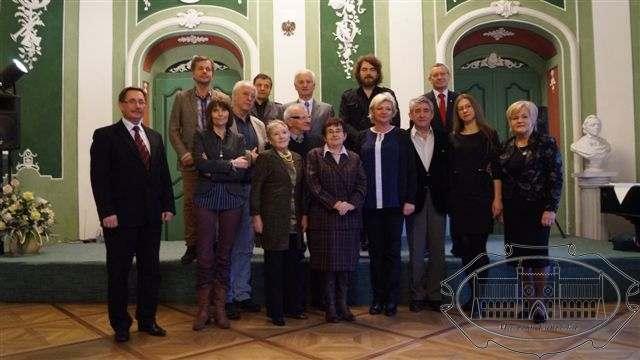 15 odświętnie ubranych osób pozuje do zdjęcia we wnętrzu pałacu