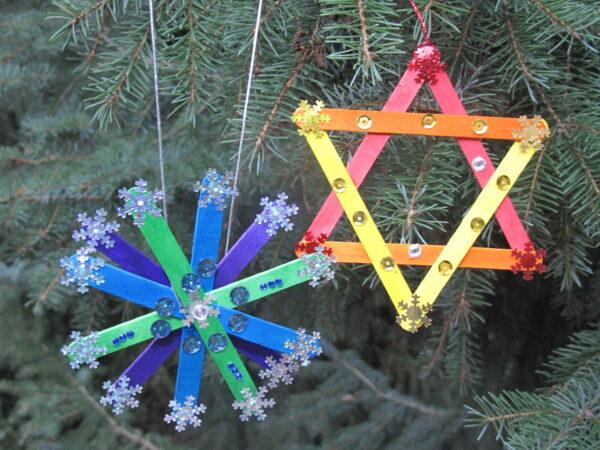 Zdjęcie przedstawiające dwie własnoręcznie wykonane kolorowe ozdoby choinkowe na tle choinkowych gałęzi