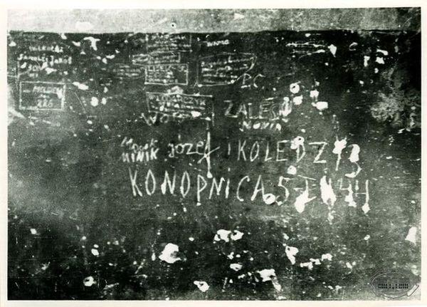 Zdjęcie obdrapanej ściany z wyrytymi napisami