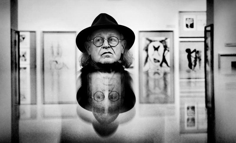 Czarno-białe zdjęcie - w centrum głowa Tadeusza Mysłowskiego, poniżej jej lustrzane odbicie. Mężczyzna ma na głowie kapelusz, nosi okulary. Ma poważną minę. W tle widok oprawionych i wiszących na ścianie grafik.