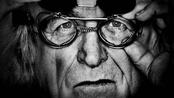 Czarno-białe zdjęcie - zbliżenie na twarz Tadeusza Mysłowskiego. Artysta nosi okulary, ma poważny wyraz twarzy.
