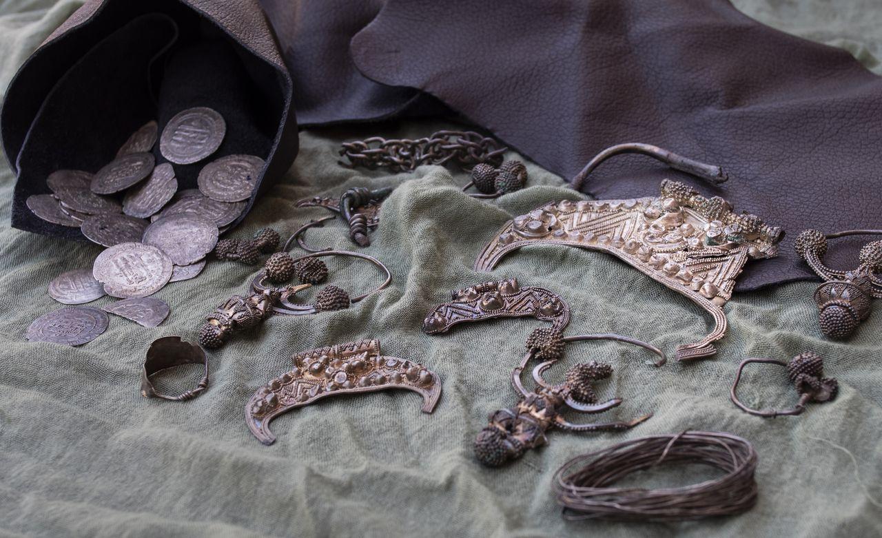 Zdjęcie Skarbu z Pińska: w lewym górnym rogu fioletowa sakiewka z wysypującymi się z niej monetami; obok ozdobna biżuteria. Przedmioty rozłożone są na szarej tkaninie. W prawym górnym rogu fragment fioletowej skóry.