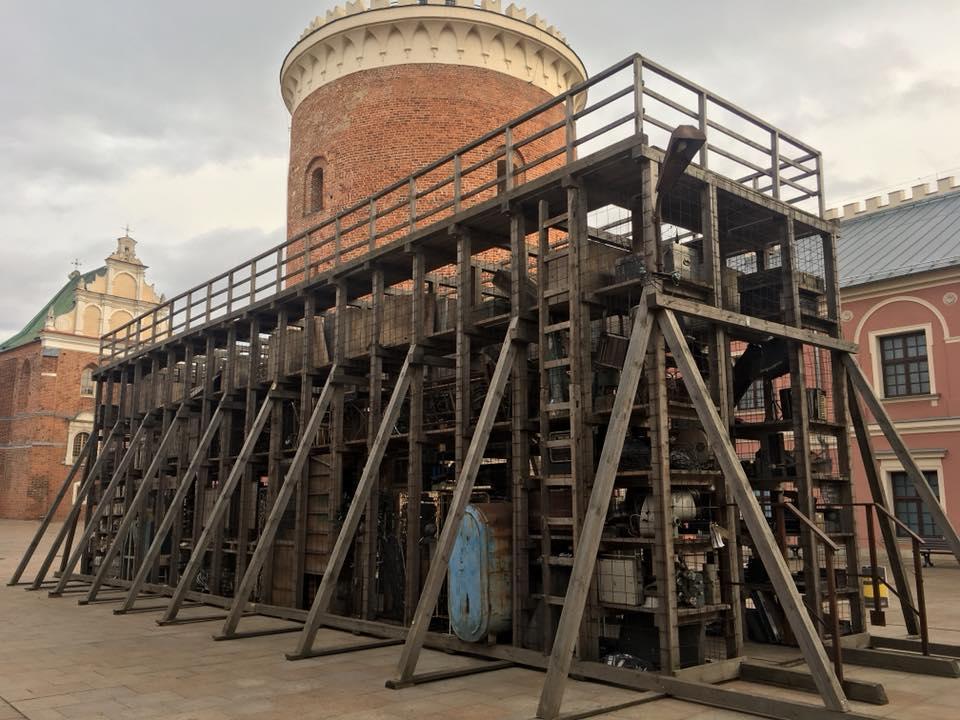 Instalacja Roberta Kuśmirowskiego na dziedzińcu Zamku Lubelskiego. Konstrukcja wykonana z drewna, w niej zgromadzone różne przedmioty.