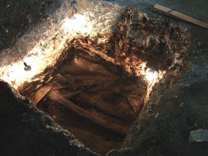 Zdjęcie przedstawiające odkrywkę archeologiczną - dół w ziemi, w którym widać fragmenty drewnianych elementów architektonicznych.