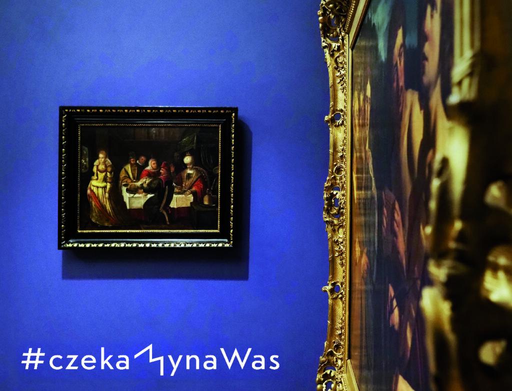 Grafika: obraz wiszący na niebieskiej ścianie przedstawiający ludzi siedzących przy stole. Poniżej biały napis: #czekamynaWas. Z prawej strony widać drugi obraz w złotej ramie ujęty w skrócie perspektywicznym.