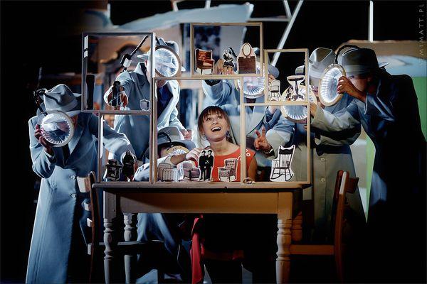 Młoda uśmiechnięta kobieta przy stole z rekwizytami teatralnymi, wokół niej ubrani w płaszcze i kapelusze mężczyzni