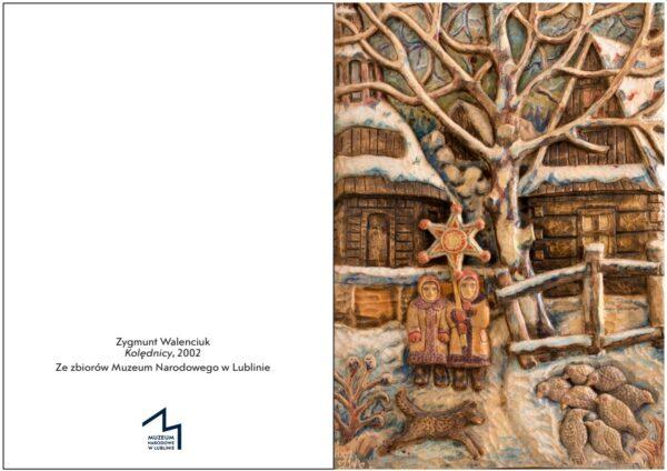 Kartka świąteczna przedstawiająca pracę Zygmunta Walenciuka pt. Kolędnicy - drewniana płaskorzeźba ukazuje dwójkę kolędników z gwiazdą na tle drewnianych domów, w centrum drzewo, na dole zwierzęta