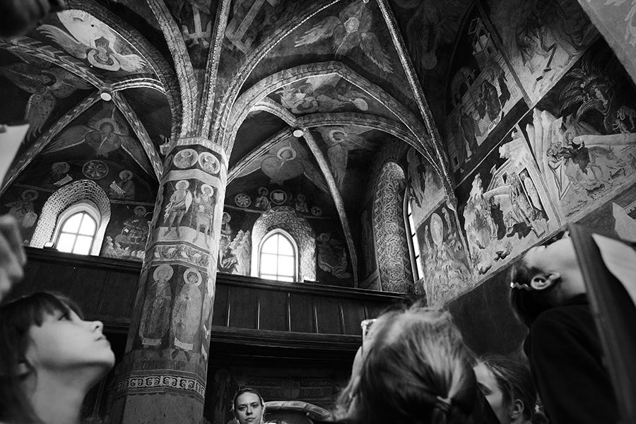 Czarno-białe zdjęcie przedstawiające fragment sklepienia Kaplicy Trójcy Świętej na Zamku Lubelskim. U dołu widać zadarte głowy zwiedzających.