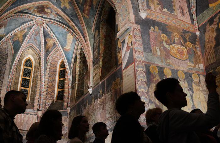 Zdjęcie fragmentu wnętrza Kaplicy Trójcy Świętej na Zamku Lubelskim, na pierwszym planie zarysy zwiedzających.
