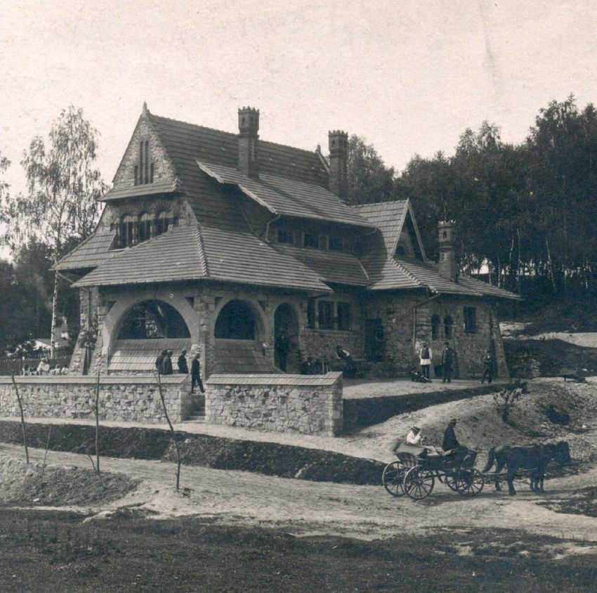 Czarno-białe zdjęcie przedstawia dom w stylu zakopiańskim - murowany z drewnianym, spadzistym dachem. W tle las. Wokół domu zebrani w mniejsze grupki ludzie. W prawym dolnym dolnym rogu dorożka.