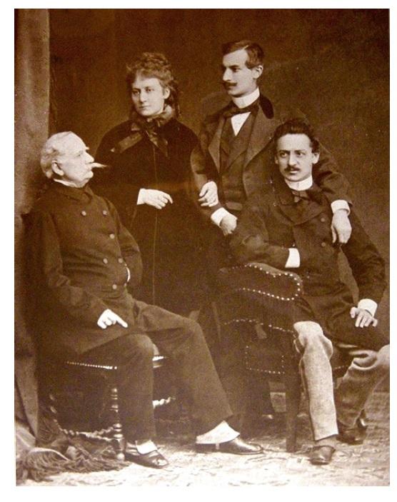 Fotografia trzech mężczyzn i jednej kobiety w strojach z XIX wieku