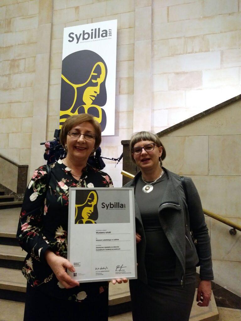 Zdjęcie dwóch uśmiechniętych  kuratorek wystawy, kobieta z lewej strony trzyma wyróżnienie, w tle schody i plakat konkursu na ścianie.