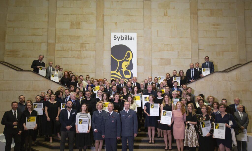 Zdjęcie pamiątkowe uczestników konkursu na reprezentacyjnej klatce schodowej, niektórzy z nich trzymają wyróżnienia. W tle na ścianie plakat konkursu.