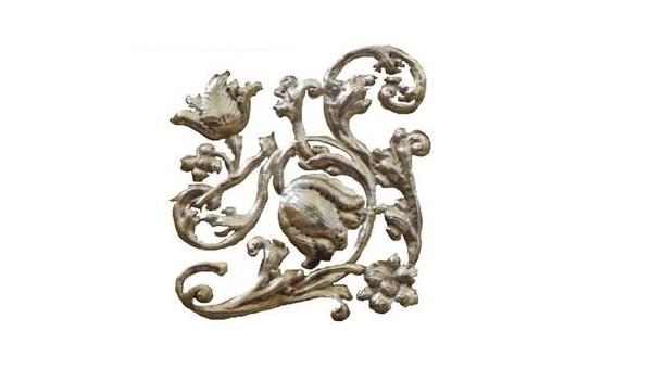 Zdjęcie kwiatowego ornamentu wykonanego z metalu, prawdopodobnie ze złota.